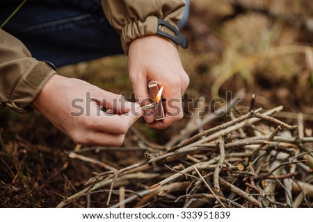 camper holds a lit match under the kindling to start a camp fire - stock photo