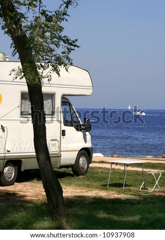 Camper parked at see, near a road - stock photo