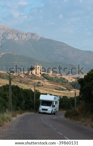 Camper / Trailer / Mobile home / Recreational vehicle / Motor caravan on the move within the beautiful landscape of Corsica, France - stock photo