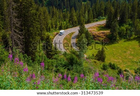 Camper Van Summer Travel. Rving Photo Theme. Small Class C Travel Camper on a Mountain Road During Summer Time. - stock photo