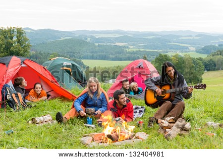 Campers in tents listening to girl playing guitar beside campfire - stock photo