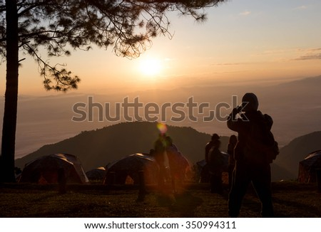Campers taking a picture of sunrise with smart phone in silhouette background - stock photo
