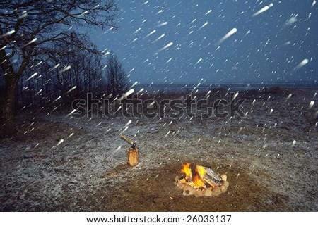 Campfire and snowfall at night - stock photo