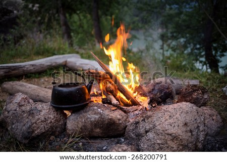 Campfire and the old kettle in twilight - stock photo