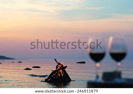 Campfire and wine glasses with wine on the coast - stock photo