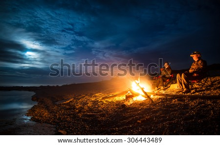 Campfire on a rocky beach with a couple sitting - stock photo