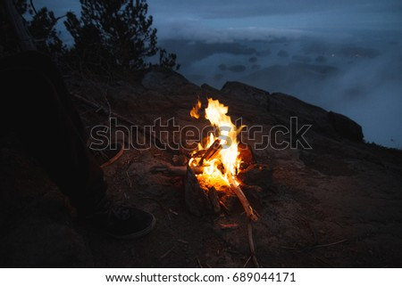 Campfire on the edge with campfire above bay with islands and forests in cloudy weather from top view in the evening