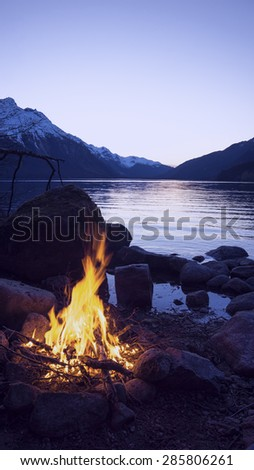 Campfire on the shores of Chilkoot Lake in Alaska in evening light. - stock photo