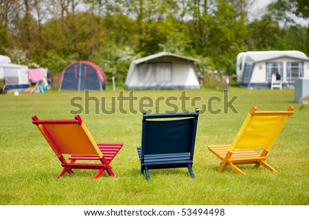 Campground with colorful empty chairs to sit down - stock photo