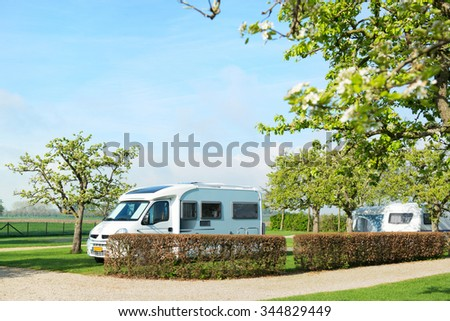 Campground with mobile home and caravan in spring - stock photo