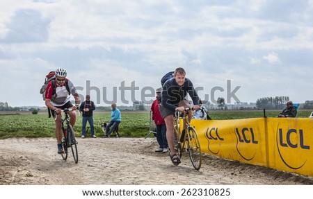 CAMPHIN EN PEVELE,FRANCE-APR 13:Amateurs riding before the apparition of the peloton on the cobblestone sector Carrefour de Arbre in Camphin-en-Pevele on April 13 2014 during Paris-Roubaix race - stock photo