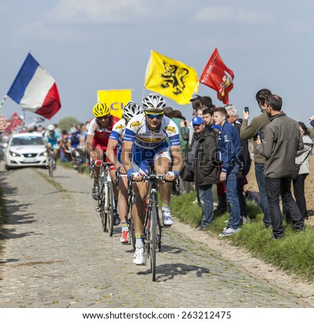 CAMPHIN EN PEVELE,FRANCE-APR 13:Edward Theuns riding in front of a group of riders, on the cobblestone sector Carrefour de Arbre in Camphin-en-Pevele on April 13 2014 during Paris-Roubaix  - stock photo