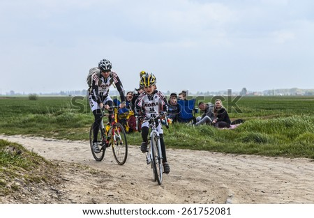 CAMPHIN EN PEVELE,FRANCE-APR 13: Image of a kid and his father cycling on the cobblestone sector Carrefour de Arbre in Camphin-en-Pevele on April 13 2014 during Paris-Roubaix cycling race - stock photo