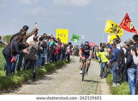 CAMPHIN EN PEVELE,FRANCE-APR 13:The cyclist Roger Kluge from Team IAM Cycling riding on the cobblestone sector Carrefour de l'Arbre in Camphin-en-Pevele on April 13 2014 during Paris-Roubaix race - stock photo