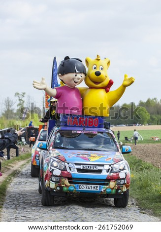 CAMPHIN EN PEVELE,FRANCE-APR 13: Vehicles of Haribo during the passing of Publicity Caravan on the cobblestone road in Camphin-en-Pevele on April 13 2014 during Paris-Roubaix cycling race - stock photo