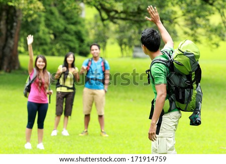 camping concept. young man leaving his friends after camping in the park - stock photo