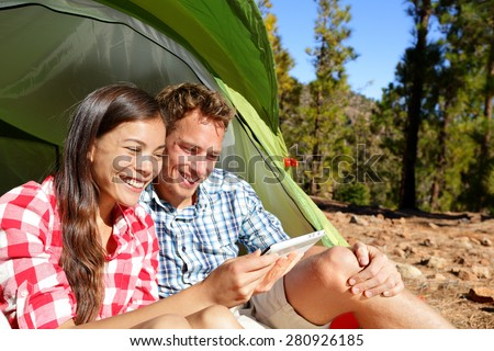 Camping couple in tent using smartphone or small tablet looking at pictures photos. Campers smiling happy outdoors in forest. Happy multiracial couple having fun outdoor. Asian woman, Caucasian man - stock photo