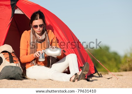 Camping happy woman front of tent on beach blue sky - stock photo