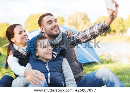 camping, hike, technology and people concept - happy family with smartphone taking selfie at campsite - stock photo