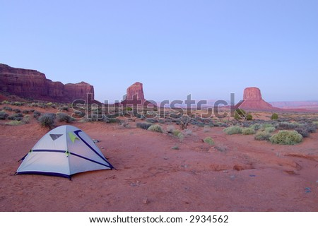 Camping in Monument Valley, Navajo Nation: a small tent in the desert with mesas lit by rising sun in the background. - stock photo