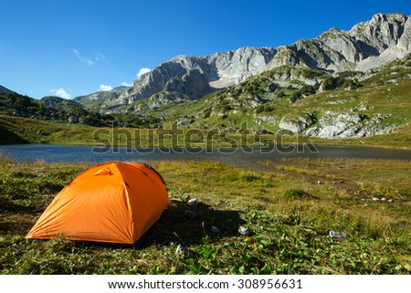 camping in mountain lake on green grass - stock photo