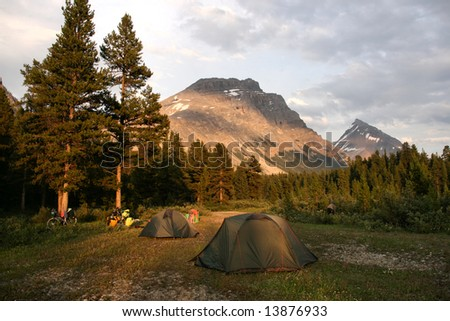 Camping in Rocky Mountains of Canada. Banff National Park, Alberta. Tents in the sunset light. - stock photo