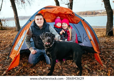Camping in tent - family with dog camping in autumn forest  - stock photo