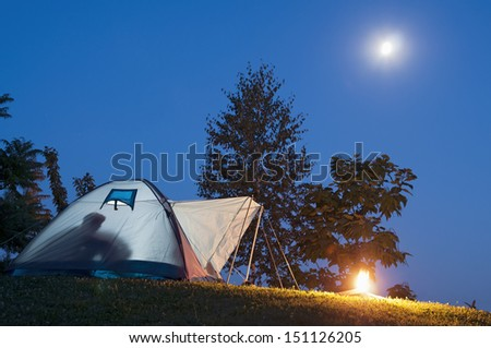 Camping in tent with human shadow and campfire, moon and stars on the clear blue sky - stock photo