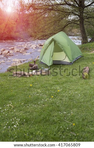 Camping in the woods on the banks of the river. - stock photo