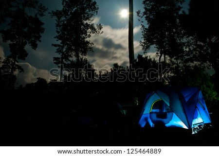Camping in the woods under the moonlight - stock photo