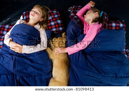 Camping kids and a puppy sleeping in a tent. - stock photo