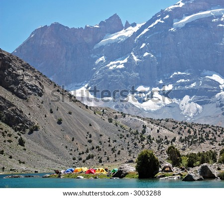 Camping near the mountain wall. - stock photo
