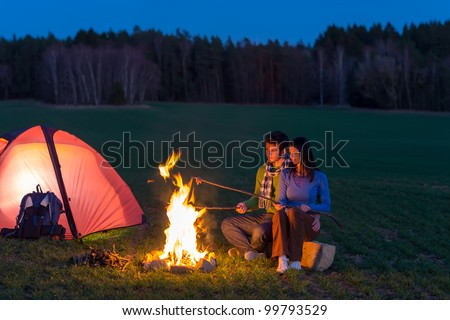 Camping night couple cook by campfire backpack in romantic countryside - stock photo