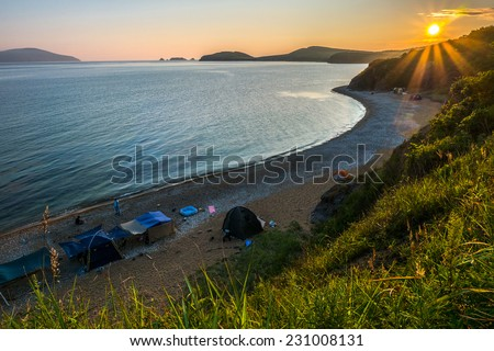 camping on the beach against sunset of russian isle Putyatin  - stock photo