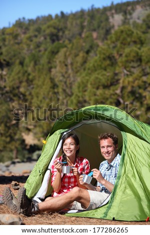 Camping people - couple eating food in tent smiling happy outdoors in forest. Happy multiracial couple having fun relaxing after outdoor activity hiking. Asian woman, Caucasian man. - stock photo