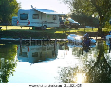 Camping site on a lake with caravans and boats - stock photo