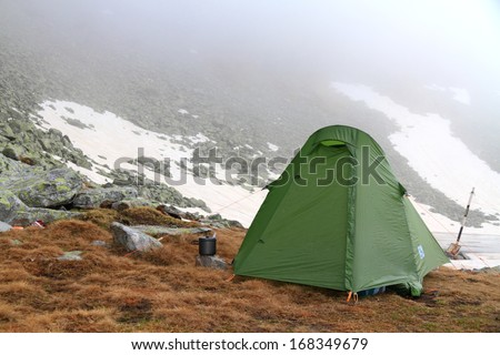Camping site on the mountain and green tent in bad weather - stock photo
