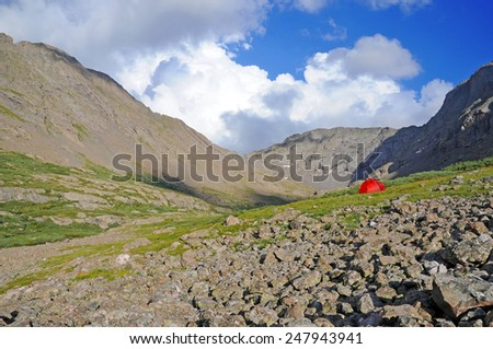 Camping tent in alpine scene with mountain backdrop - stock photo
