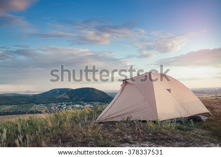 Camping tent in the countryside. Summer, blue sky, clouds and green hills