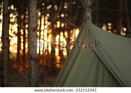 Camping tent in the forrest with sunset - stock photo