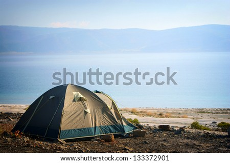 Camping tent in the nature. Mountains and lake.