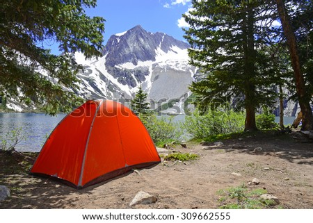 Camping tent in the Rocky Mountains with lake and snow capped peaks - stock photo