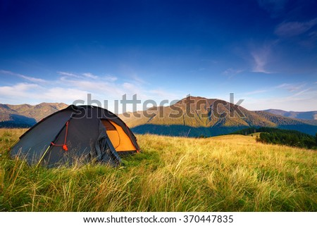 Camping tent on the mountain meadow after the dawn. Blue sky over hills