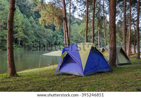 Camping tents in pine tree forest near lake at Pang Oung national park in Mae Hong Son, Thailand - stock photo