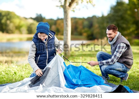 camping, tourism, hike, family and people concept - happy father and son setting up tent outdoors - stock photo