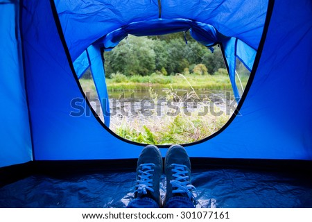 camping, travel, tourism, hike and people concept - close up of camper legs lying near blur tent entrance and enjoying natural landscape - stock photo