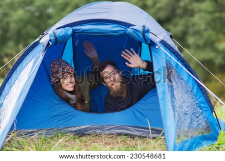 camping, travel, tourism, hike and people concept - smiling couple of tourists looking out from tent and waving hands - stock photo