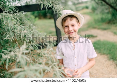 Camping under the trees boy in a straw hat and a white shirt