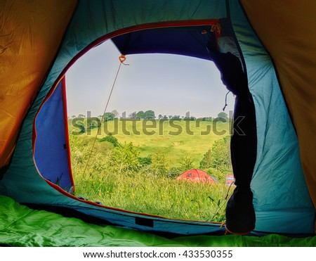 Camping, View from inside a tent looking at another tent on a campsite field. - stock photo
