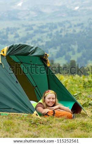 Camping woman resting in front of  tent on  nature - stock photo